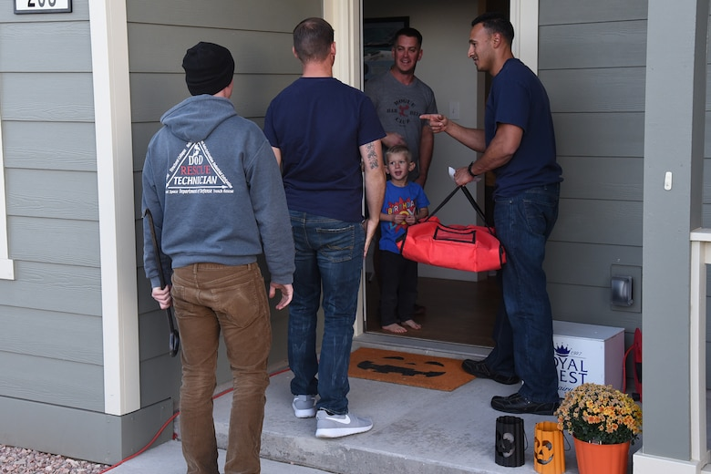 21st Civil Engineer fire fighters deliver pizza to a family at Tierra Vista housing on Peterson Air Force Base, Colorado, Oct. 13, 2017. The pizza was free if the family agreed to a fire inspection of their home. (U.S. Air Force photo by Robb Lingley)