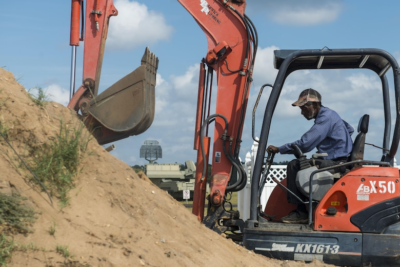 Selvin Nelson, contractor, uses an excavator to prepare the ground for water and sewer line placement at Poinsett Electronic Combat Range, near Wedgefield, S.C., Oct. 11, 2017.