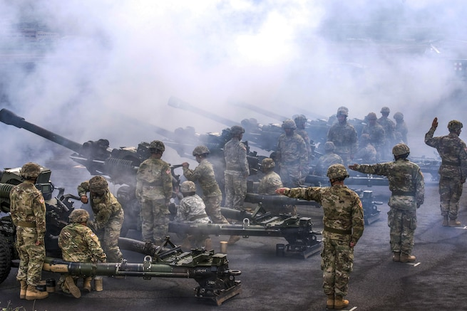 Soldiers line up and fire large weapons.