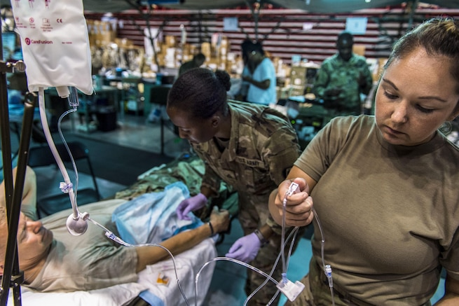A soldier gives a IV to a commander during training in a hospital.