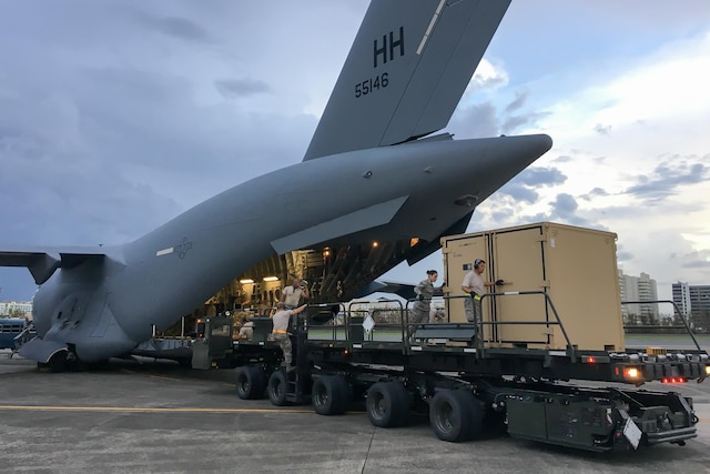 Guardsmen unload equipment from a large airplane.