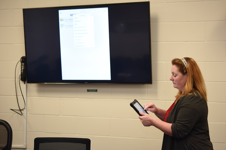 Tanya Davis, 312th Training Squadron chief of training development, demonstrates how the Fire MILE (Mobile Interaction Learning Environment) can benefit from the AirPlay feature of an iPad at the Louis F. Garland Department of Defense Fire Academy on Goodfellow Air Force Base, Texas Oct. 13, 2017. With AirPlay the trainees and instructors could share with the class any e-book, application, or training video with ease by simply displaying their iPad onto a television screen. (U.S. Air Force phot by Airman 1st Class Zachary Chapman/Released)