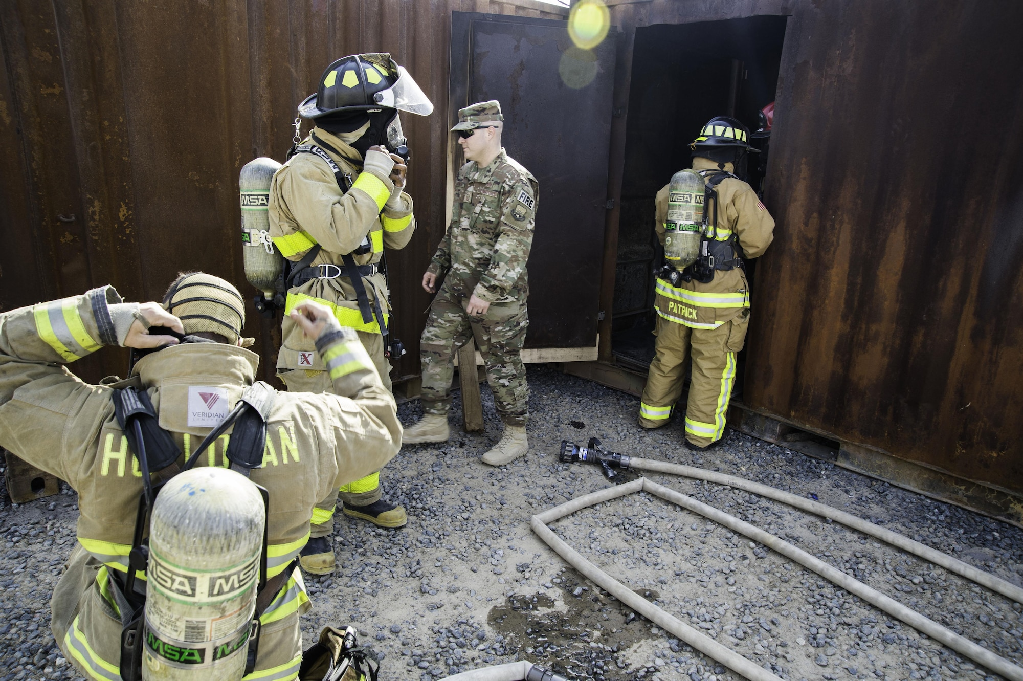 Airmen from the 386th Expeditionary Civil Engineer Squadron Fire Department prepare to enter a live fire training facility at an undisclosed location in Southwest Asia, Oct. 20, 2017. The live fire training comes at the heels of National Fire Prevention week, which encouraged people to have multiple plans of escape in case of an emergency. (Air Force photo by Staff Sgt. William Banton)