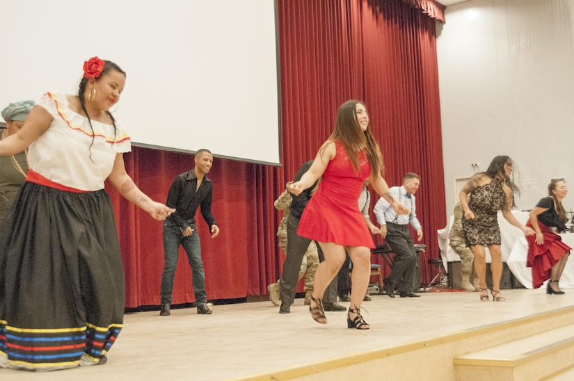 Group of men and women on stage performing a line dance.