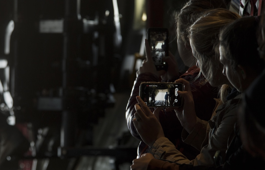 A Ramstein military spouse records a video of the ramp doors opening on a C-130J Super Hercules flying near Ramstein Air Base, Germany, Oct. 17, 2017. More than 25 military spouses participated in an incentive flight with the 37th Airlift Squadron as a part of the Ramstein Airman and Family Readiness Center's Heart Link program. (U.S. Air Force photo by Senior Airman Tryphena Mayhugh)