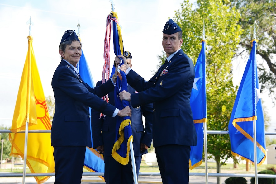 Air Force Materiel Command Commander Gen. Ellen M. Pawlikowski, passes the unit guidon to the new Air Force Nuclear Weapons Center commander Maj. Gen. Shaun Q. Morris during a change of command ceremony Oct. 6 at Hardin Field.