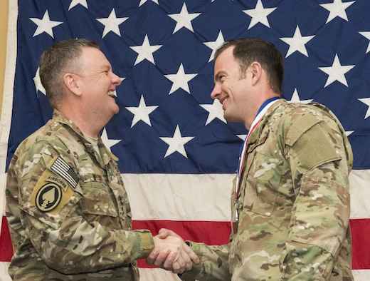 Lt. Gen. Brad Webb shaking hands with Tech. Sgt. Thomas Wojak with American flag in background.