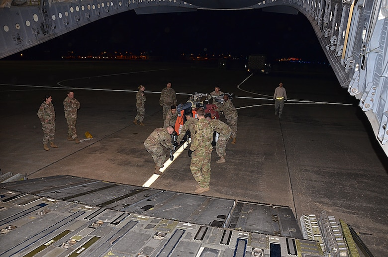 U.S. Army Soldiers assigned to the 832nd Transportation Battalion, 597th Transportation Brigade, work together to load equipment onto a U.S. Air Force Air Mobility Command C-17 at Joint Base Langley-Eustis, Va., Oct. 18, 2017.