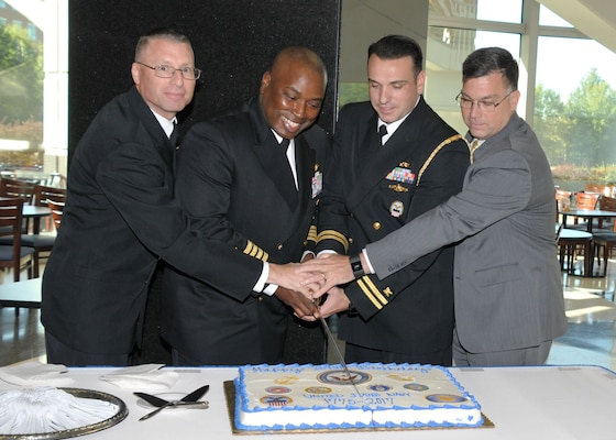 Navy personnel in class A uniforms cutting cake, facing viewer