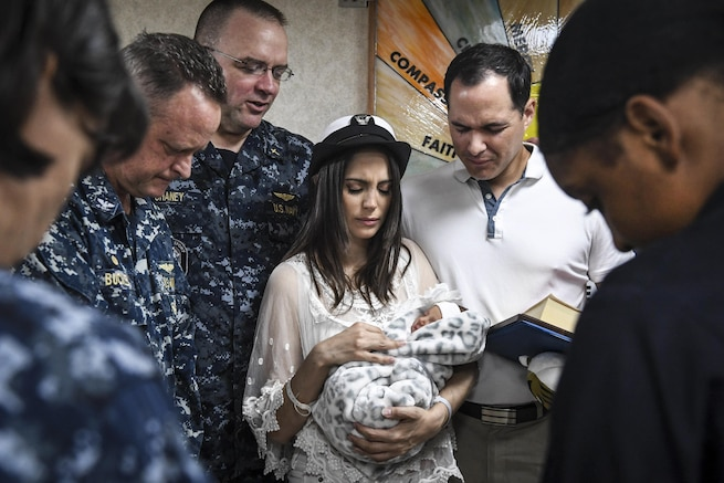 A woman holding a baby is surrounded by people with their heads lowered.