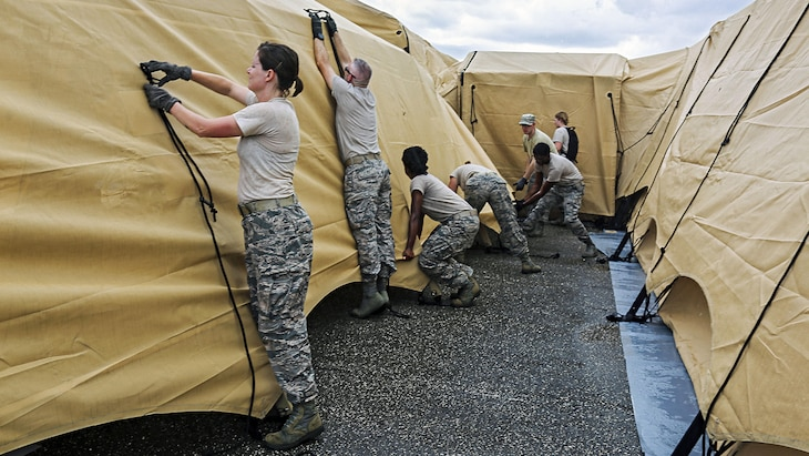 A group of guardsmen tie ropes to secure tents.