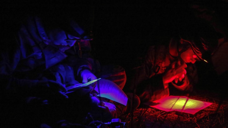 Using red and blue lights, two service members look at paperwork.