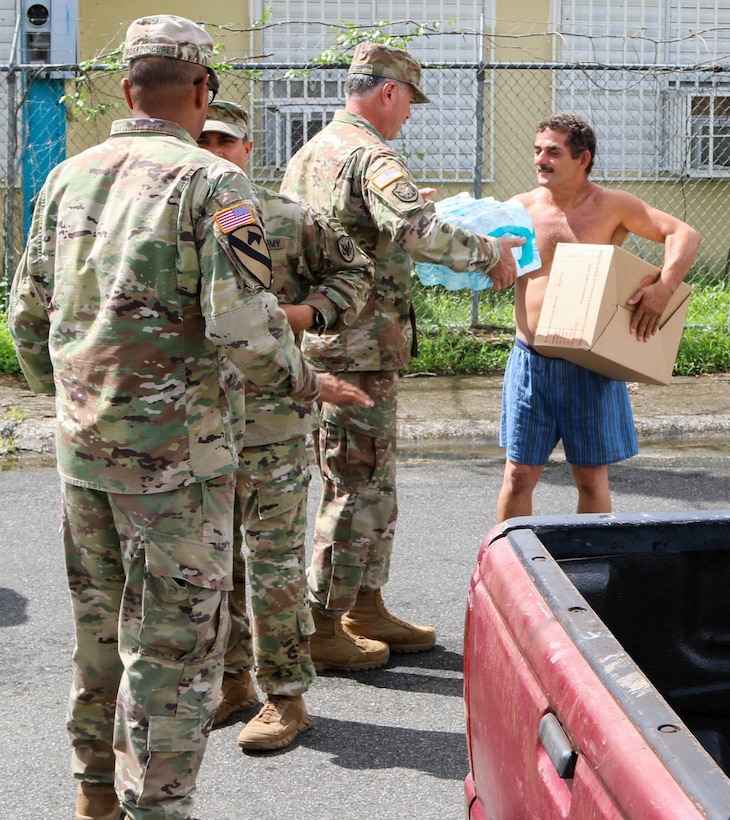Members of the Puerto Rico Army National Guard, Reserve and active duty, along with Lt. Gen. Jeffrey Buchanan, U.S. Army North commander; Brig. Gen. José Reyes, Dual Status commander; and Caguas Mayor Hon. William Miranda Torres, distributed food and water to residents of the neighborhood Borinquen, Oct. 14. Reyes, Buchanan and Marín handed over provisions to the people who were grateful for the help received and were seriously affected by Hurricane Maria.