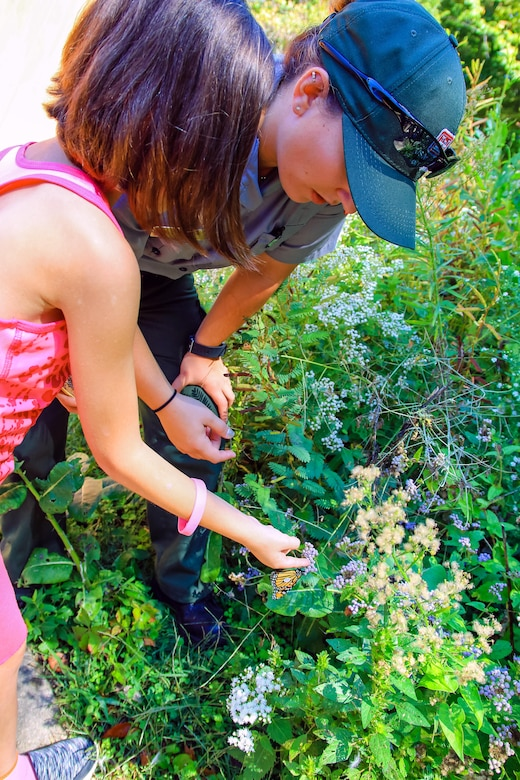 Caesar Creek Lake Ranger Taylor Guay and a visitor release a tagged monarch butterfly.