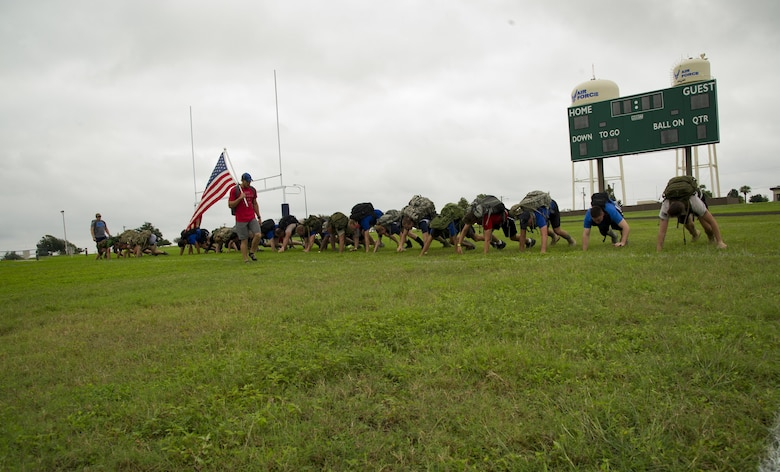 Participants in a ruck march challenge bear crawl on a sports field at Laughlin Air Force Base, Texas, Oct. 14, 2017.  The march itself started once the 23-person group finished a series of team-building exercises consisting of low crawls, crowd surfing, and bear crawls.  (U.S. Air Force photo\Airman 1st Class Daniel Hambor)