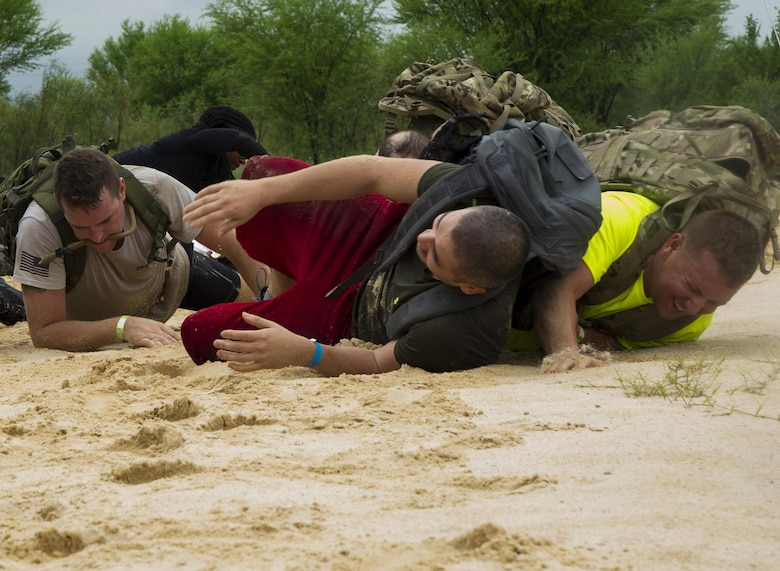 Participants in a ruck march challenge slink through a sand-filled volleyball court at Laughlin Air Force Base, Texas, Oct. 14, 2017.  The ruck, which started at Laughlin's football field and continued throughout the base, was a 10-kilometer march which contained various challenges at various points along the route. (U.S. Air Force photo\Airman 1st Class Daniel Hambor)