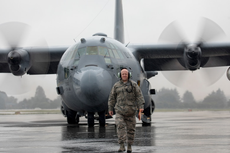Chief Master Sgt. Eric Evers, 374th Aircraft Maintenance Squadron superintendent, walks on a ramp as he marshals a C-130H Hercules at Yokota Air Base, Japan, Oct. 16, 2017.
