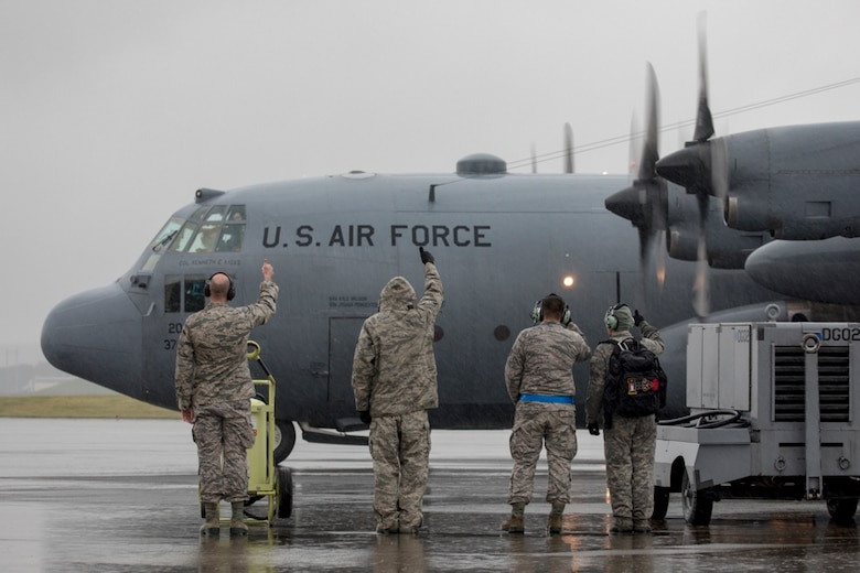 "Members with the 374th Aircraft Maintenance Squadron give a ""thumbs up"" to the aircrew on the C-130H Hercules at Yokota Air Base, Japan, Oct. 16, 2017."