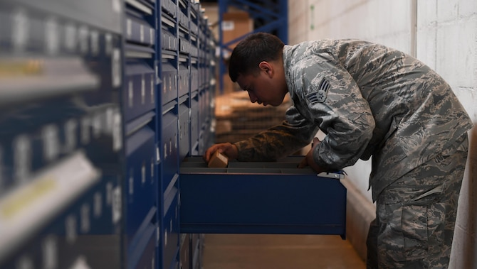 U.S. Air Force Senior Airman Julio Bonilla-Rodriguez, aircraft parts store journeyman assigned to 447th Air Expeditionary Group, grabs an ordered aircraft part from a drawer store at Incirlik Air Base, Turkey, Sept. 21, 2017. Additionally, APS provides life-saving improved outer tactical vests and enhanced small arms protective inserts to deployed personnel. (U.S. Air Force photo by Senior Airman Jasmonet D. Jackson)