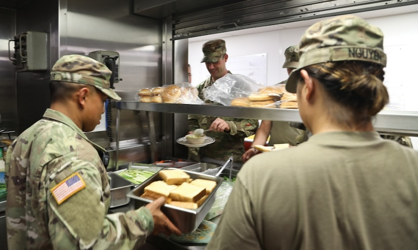 Army Sgt. James Munar, a Pomona, Calif., native and a culinary specialist with the 605th Transportation Detachment, 8th Special Troops Battalion, 8th Theater Sustainment Command, helps prepare lunch with his soldiers on the logistic support vessel, the USAV CW3 Harold A. Clinger, off the Hawaiian coast, Oct. 4, 2017. Army photo by Staff Sgt. Melissa Parrish