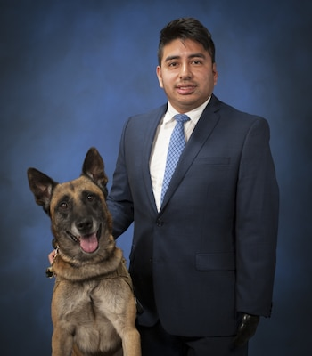 Marco Robledo, a disabled combat veteran and federal employee working at Naval Surface Warfare Center, Carderock in West Bethesda, Md., Oct. 12, 2017, poses with his service dog, Chuck Diesel. Robledo was wounded by an improvised explosive device while deployed to Iraq as a combat engineer with the National Guard in 2007. After he rehabilitated from his injuries, he followed a mentor's advice and applied to work at Carderock as a contract specialist. He spoke about being grateful for his fellow Soldiers who saved his life and for overcoming his challenges and making a good life for himself following his upbringing by struggling migrant workers. (U.S. Navy photo by Devin Pisner/Released)