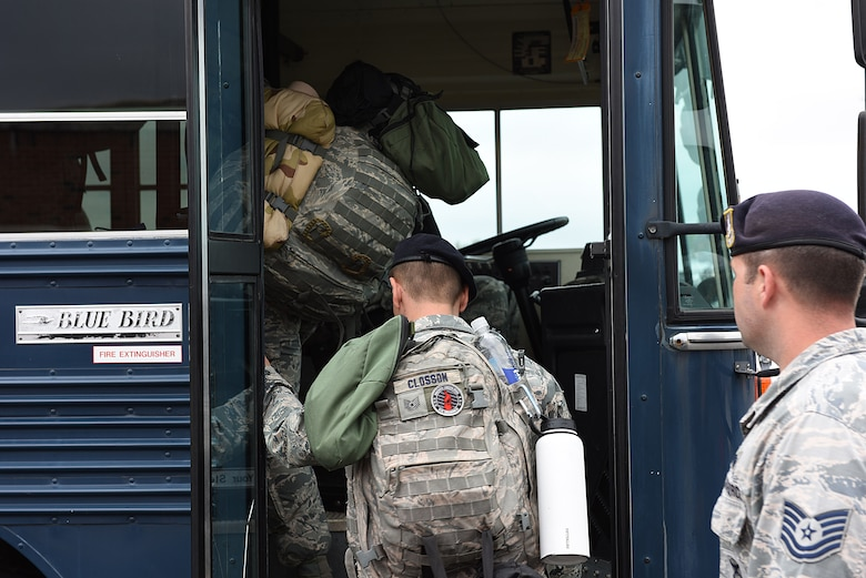 Tech. Sgt. Closson wearing a backpack boards an Air Force bus