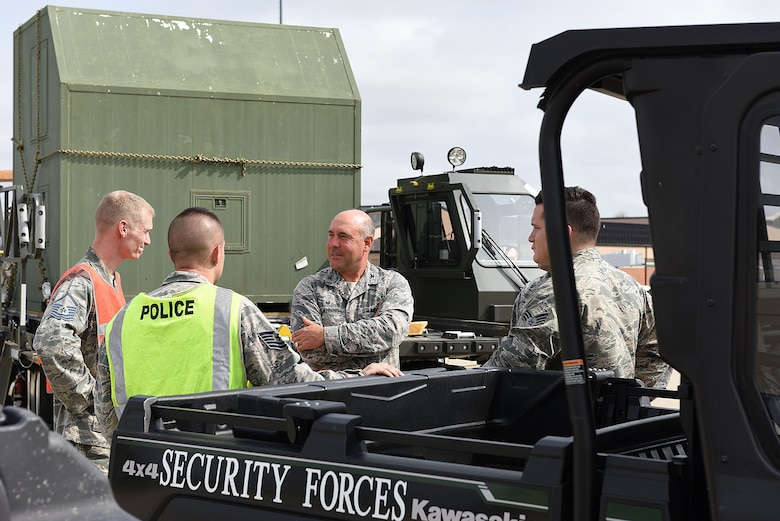 Col. Jonathan Boehning stands beside cargo pallets and all terrain vehicles talking to Security Forces personnel