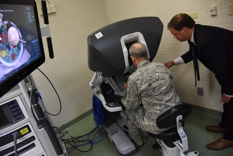 Blaise Provitola, Intuitive Surgical Inc. area sales manager, guides Lt. Gen. Mark Ediger, Air Force Surgeon General, as he operates a da Vinci surgical system, which is used for robotics surgeries, during a visit to the clinical research laboratory Oct. 17, 2017, on Keesler Air Force Base, Mississippi. The purpose of Ediger's visit was to get familiar with the 81st Medical Group's mission, operations and personnel. During his tour, he visited more than 10 different units in the 81st MDG to include mammography, emergency department, radiology and oncology, genetics and the clinical research laboratory. (U.S. Air Force photo by Kemberly Groue)