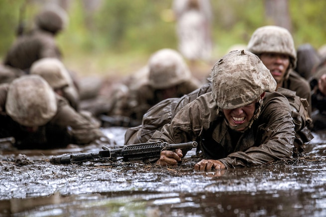 Marine recruits crawl through mud.