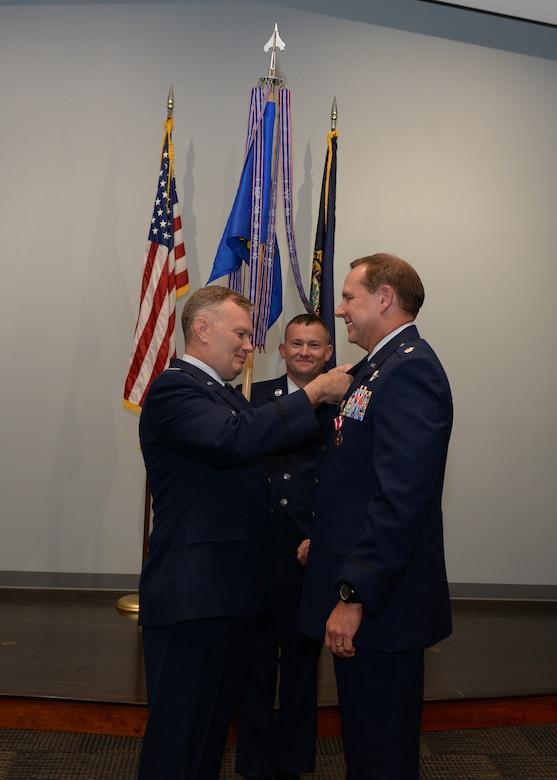 Col. John Pogorek, commander of the 157th Operations Group, left, pins a commander's pin on Lt. Col. Mark Ustaszewski, incoming commander of the 157th Operations Support Squadron during a change command ceremony as Master Sgt. Jason Veziris holds the 157th OSS unit guidon, Oct. 14, 2017,  Pease Air National Guard Base, N.H. Lt. Col. Ustaszewski replaces outgoing 157th OSS commander Lt. Col. Jeffery Cole, who served as the commander for two years and will be the new deputy commander for the 157th OG. (N.H. Air National Guard photo by Airman Victoria Nelson)