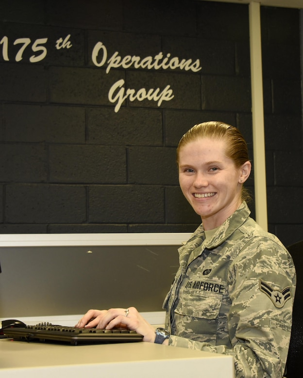 Airman 1st Class Allison Dassing poses at a desk in the 175th Operations Group Oct. 3, 2017 at Warfield Air National Guard, Middle River, Md. Dassing is a fulltime intelligence technician but in her free time enjoys spending time with family, travelling and video games. (U.S. Air National Guard photo by Senior Airman Enjoli Saunders)