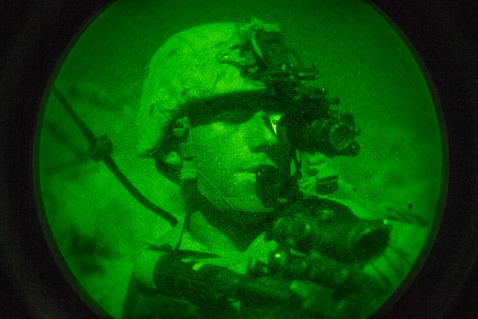 A U.S. Marine with Regimental Surveillance & Target Acquisition Company (RSTAC), 1st Marine Division, looks through a PVS-14 night vision scope during a night insert at Fort Irwin, Calif., Oct. 1, 2017.