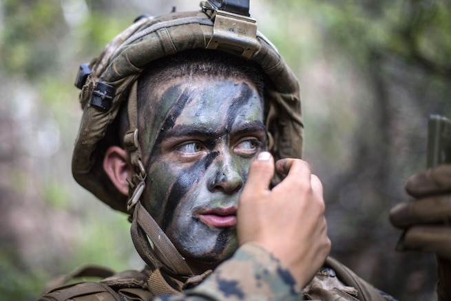 A Marine looks in a compact mirror while putting on camouflage paint in wooded surroundings.