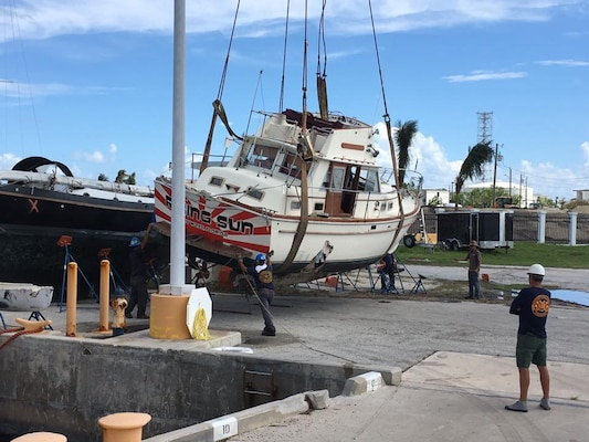 Image: Boat on a crane lift being maneuvered near Naval Air Station Key West after hurricane Irma.