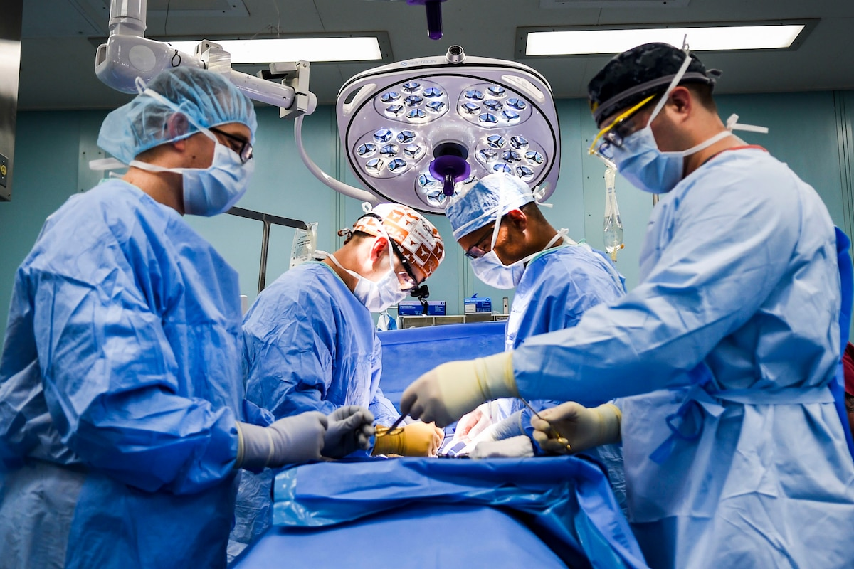 Medical personnel in blue surgical clothes perform surgery in an operating room.