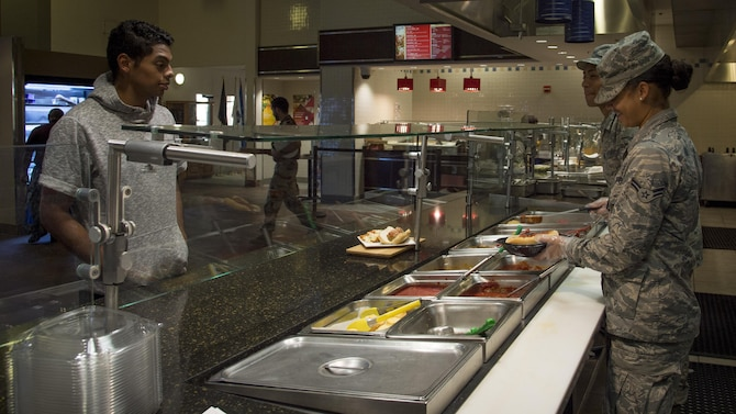 U.S. Air Force Airman 1st Class Antigone Falkner, right, and Airman 1st Class Randall Bagtas, both services apprentices assigned to the 6th Force Support Squadron, assists a customer in the dining facility at MacDill Air Force Base, Fla., Oct. 19, 2017. The MacDill dining facility serves approximately 800 to 1,000 customers daily. (U.S. Air Force photo by Senior Airman Mariette Adams)