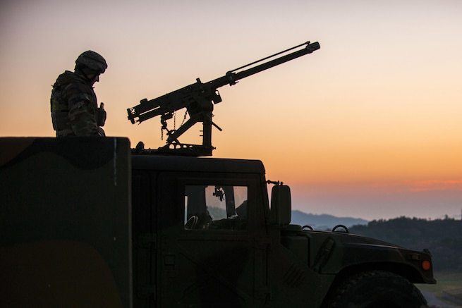An airman, shown in silhouette, sits atop a vehicle and mans a machine gun.