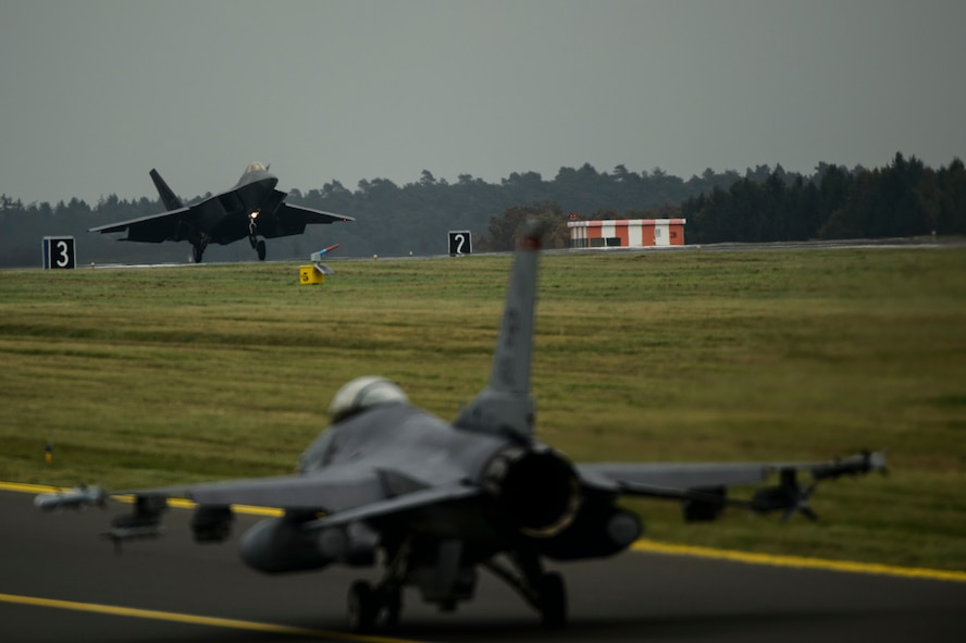 An F-22 Raptor assigned to the 1st Fighter Wing, Joint Base Langley-Eustis, Va., lands while an F-16 Fighting Falcon assigned to the 480th Fighter Squadron taxis at Spangdahlem Air Base, Germany, Oct. 13, 2017.
