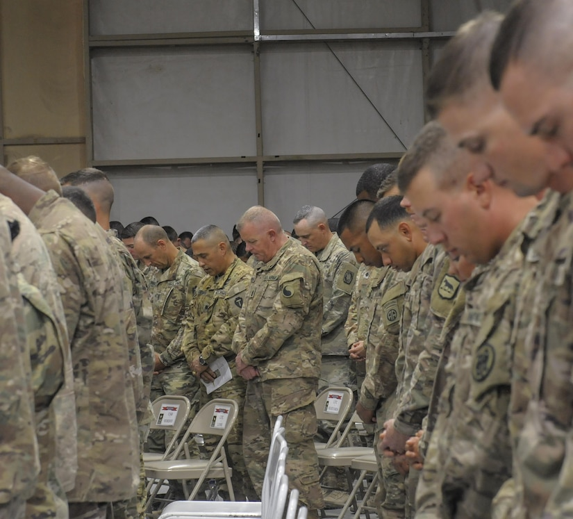 Soldiers bow their heads during a prayer.