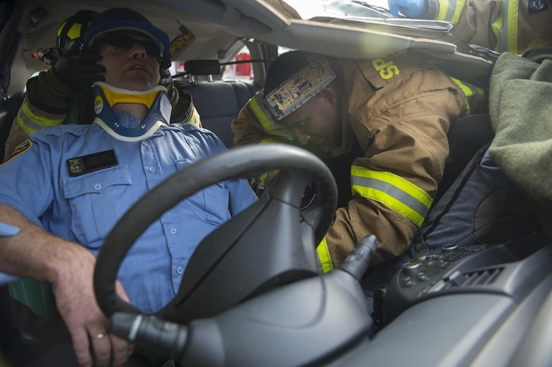U.S. Air Force Senior Airman Robert Jones, 52nd Civil Engineer Squadron firefighter, extracts Karsten Kurtze, 52nd CES Spangdahlem fire and emergency services, during a simulated vehicle accident on Spangdahlem Air Base, Germany, Oct. 19, 2017. Airmen from the 52nd CES and 52nd Medical Operations Support Squadron train together to practice and execute skills needed for real world scenarios.