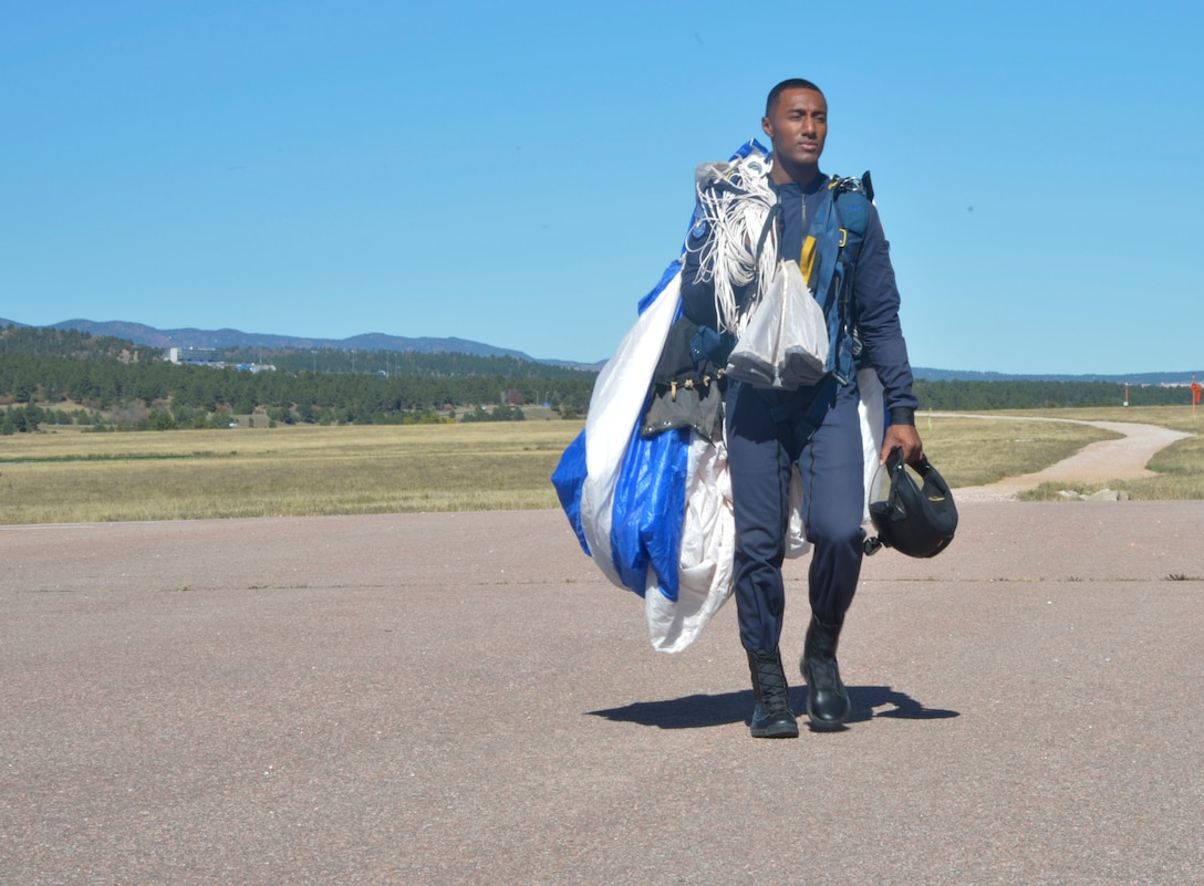 Cadet Raymone Jackson, demonstration team member for the Wings of Blue, walks back after another successful jump Oct. 12, 2017, at Peterson Air Force  Base, Colo. Jackson was enlisted for three years before coming to the Air Force Academy and joining the Wings of Blue.