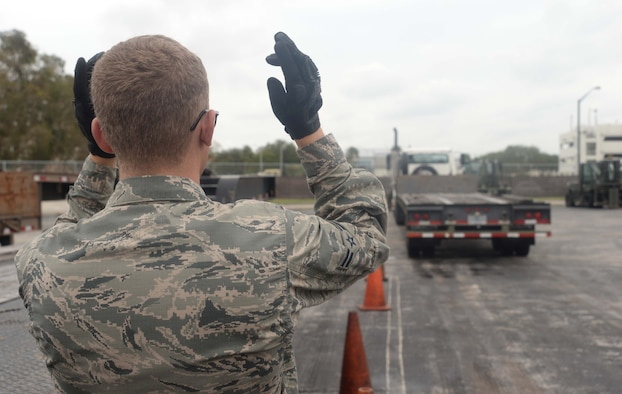 U.S Air Force Airman 1st Class Brandon Gray, a vehicle operator with the 6th Logistics Readiness Squadron, signals a tractor trailer on MacDill Air Force Base, Fla. Oct. 17, 2017.