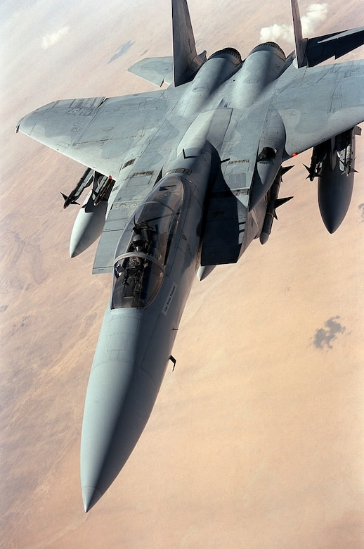An F-15 Eagle aircraft flies a patrol over the desert during the cease-fire between coalition and Iraqi forces following Operation Desert Storm.  The aircraft is carrying four AIM-9 Sidewinder missiles on its wing pylons and an AIM-7 Sparrow missile beneath its fuselage.