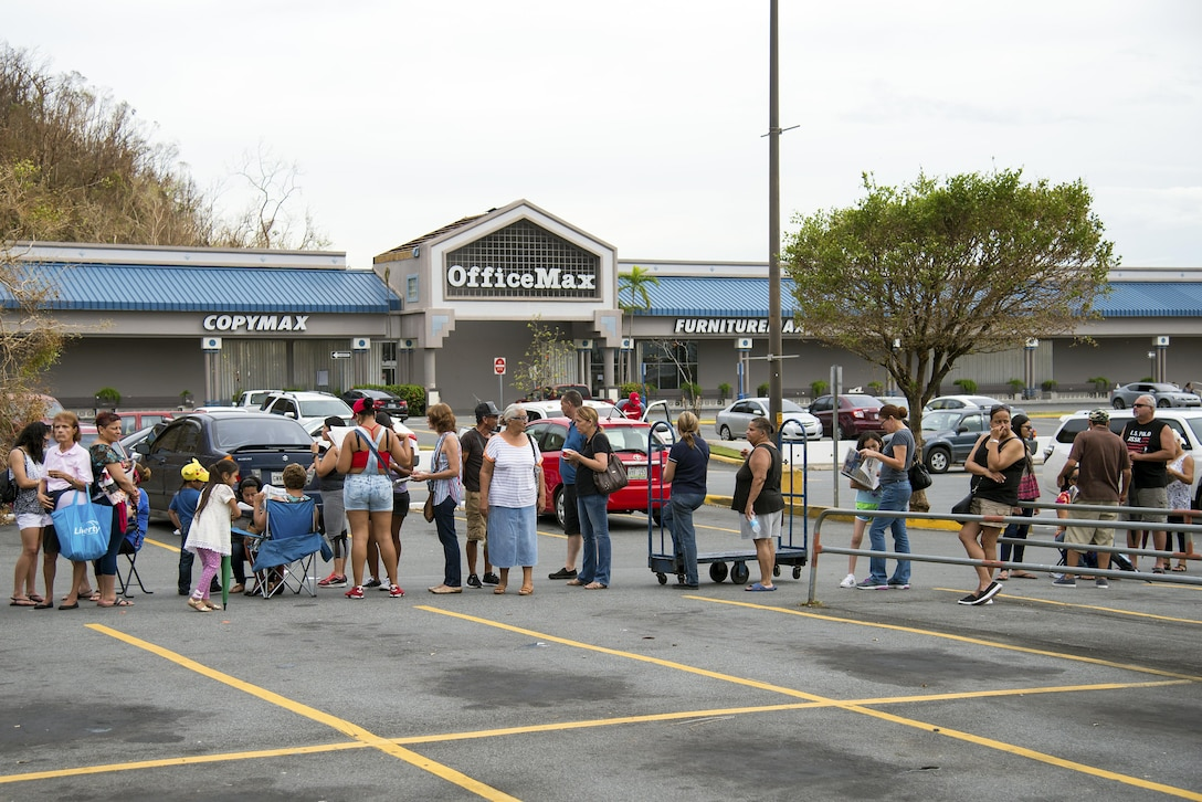 Citizens of Puerto Rico line up to buy essential supplies in Bayamon, Puerto Rico, Sept. 30, 2017. Due to the line's length, people brought their own chairs to comfortably wait for an opportunity to purchase food and water rations