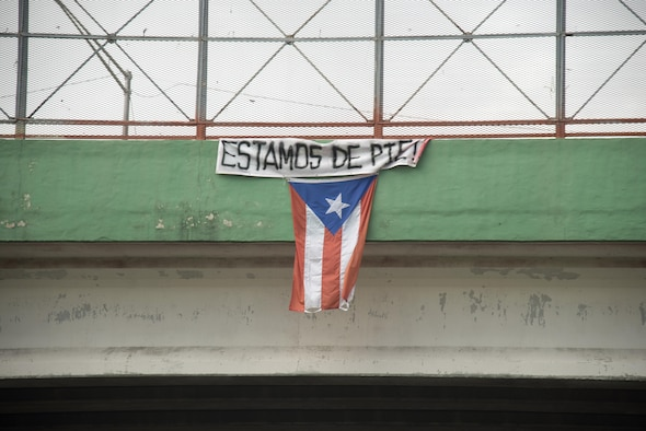 "A flag hangs from a highway overpass that reads ""Estamos de pie,"" in Caguas, Puerto Rico, Oct. 2, 2017. ""Estamos de pie"" translates to ""We are standing,"" which is meant to motivate people to stay strong and overcome the disaster left behind Hurricane Maria."