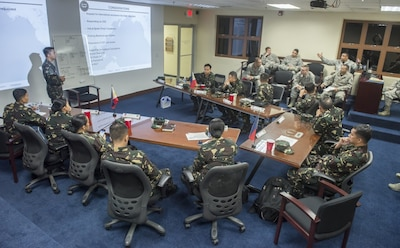 Members of the Philippine air force brief American airmen assigned to the 36th Contingency Response Group after a disaster response planning tabletop exercise during Pacific Responder 17 at Andersen Air Force Base, Guam.