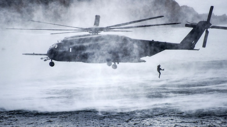 A diver jumps from a hovering helicopter into water.