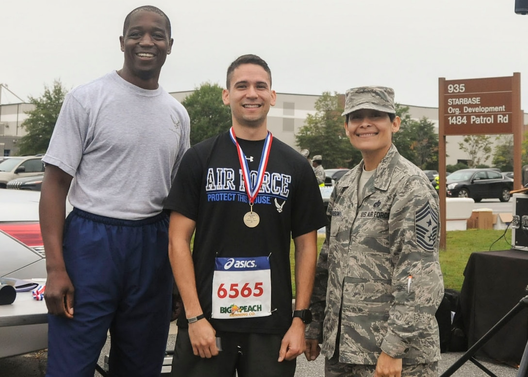 The first-place winner of this year's Falcon 5K, center, poses for a photo with Col. Patrick Campbell and Chief Master Sgt. Imelda Johnson Oct. 15, 2017. Flynn took home the first place title once again for the fifth year in a row. (U.S. Air Force photo/Senior Airman Justin Clayvon)