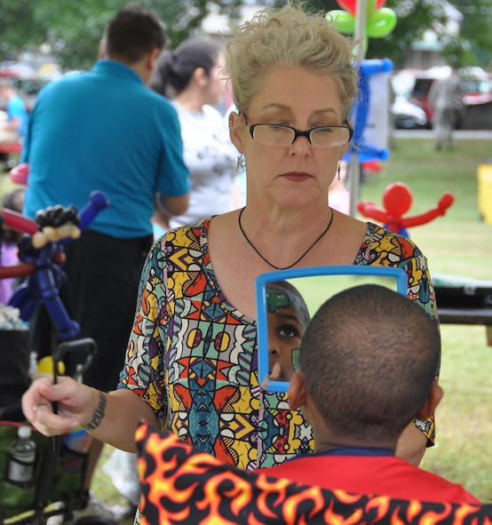 A face painter holds up a mirror to a young boy who just had his face painted at this year's Family Day Oct. 14, 2017 at Dobbins Air Reserve Base, Ga. Family Day is held here annually as a way of bringing families on base to see what their Reserve Citizen Airmen do on drill weekends. (U.S. Air Force photo/Master Sgt. James Branch)