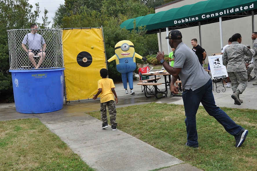 A man throws a ball at a dunk tank target at this year's Family Day Oct. 14, 2017 at Dobbins Air Reserve Base, Ga. Family Day is held here annually as a way of bringing families on base to see what their Reserve Citizen Airmen do on drill weekends. (U.S. Air Force photo/Master Sgt. James Branch)